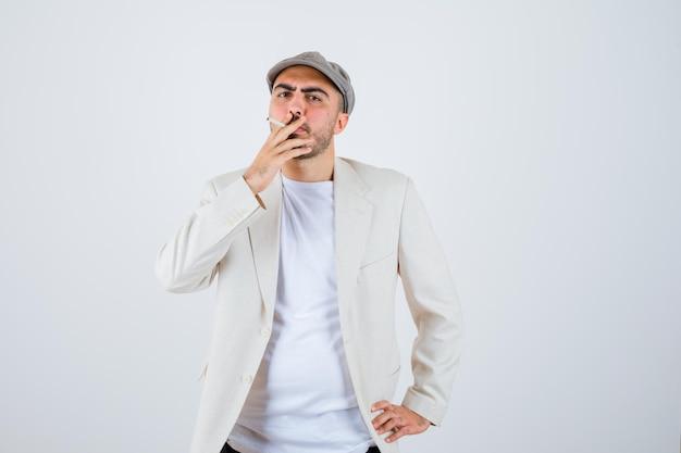 Junger mann, der hände an der taille hält, während er in weißem t-shirt, jacke und grauer mütze raucht und wütend aussieht looking