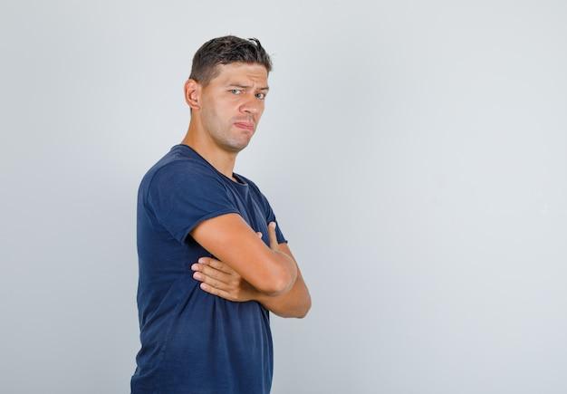 Junger mann, der hände auf brust mit stirnrunzelnden augenbrauen im dunkelblauen t-shirt faltet und selbstbewusst aussieht.