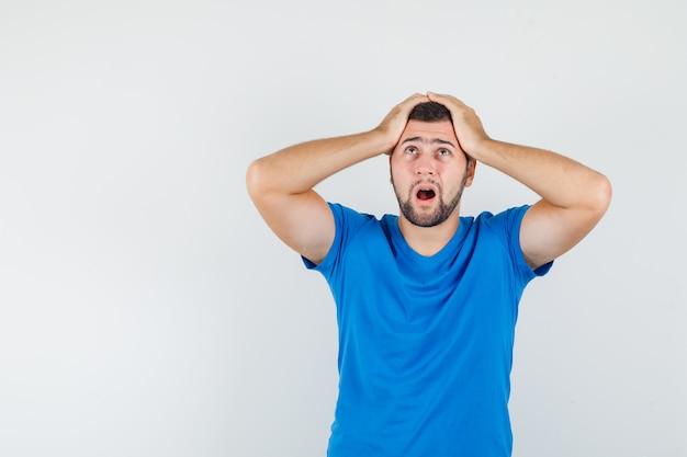 Junger mann, der hände auf kopf im blauen t-shirt hält und hilflos schaut