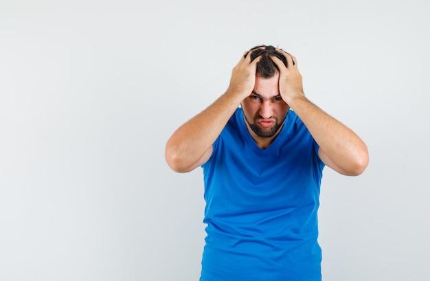 Junger mann, der hände auf kopf im blauen t-shirt hält und nervös schaut