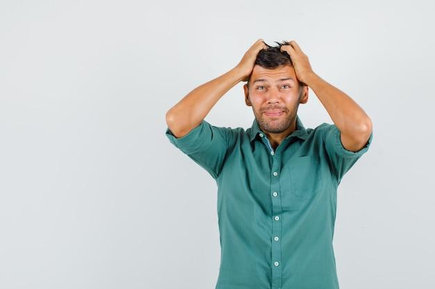 Junger mann, der hände auf kopf im hemd hält und genervt aussieht.