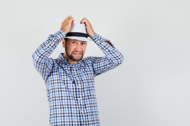 Junger mann, der hände auf kopf im karierten hemd, im hut hält und bedauernd schaut. vorderansicht.