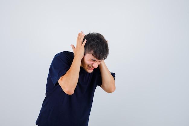 Junger mann, der hände auf ohren im schwarzen t-shirt hält und gereizt aussieht. vorderansicht.