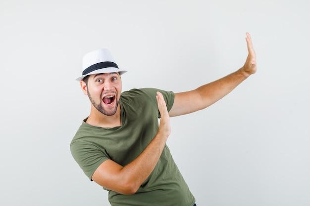 Junger mann, der hände auf vorbeugende weise in grünem t-shirt und hut erhebt und positiv schaut