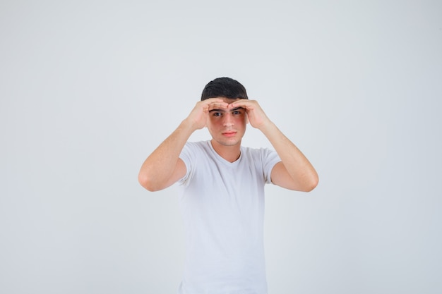 Junger mann, der hände hält, um im t-shirt klar zu sehen und konzentriert zu schauen. vorderansicht.