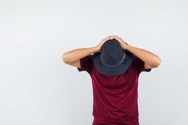 Junger mann, der hände hinter gesenktem kopf im t-shirt hält, vorderansicht des hutes.