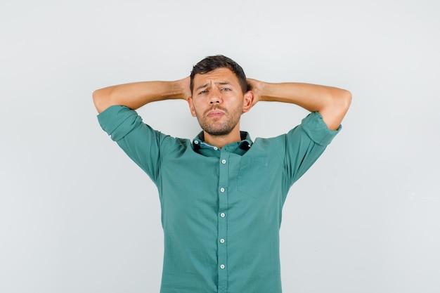 Junger mann, der hände hinter kopf im hemd hält und nachdenklich schaut
