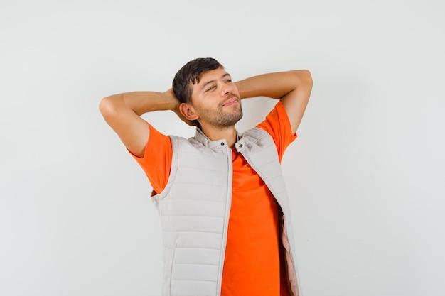 Junger mann, der hände hinter kopf in t-shirt, jacke hält und entspannt schaut. vorderansicht.