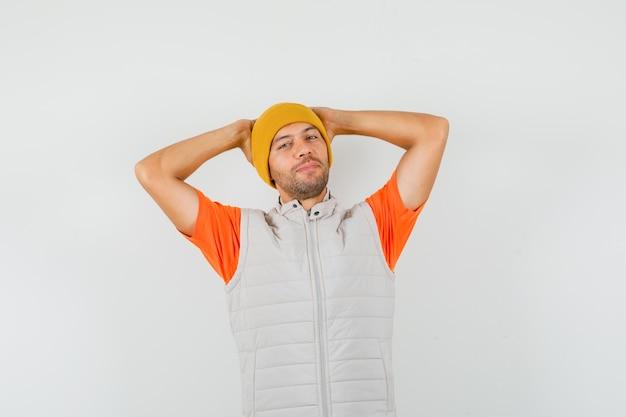 Junger mann, der hände hinter kopf in t-shirt, jacke, hut hält und entspannt schaut. vorderansicht.