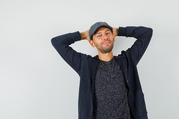 Junger mann, der hände hinter kopf in t-shirt, jacke, mütze hält und entspannt schaut. vorderansicht.