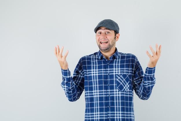Junger mann, der hände im hemd, in der mütze und in der fröhlichkeit, vorderansicht erhebt.