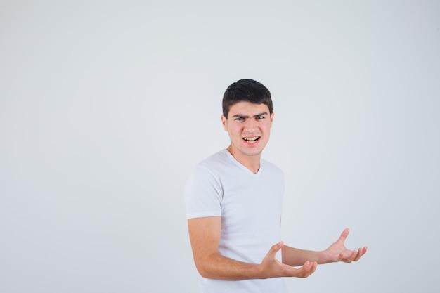 Junger mann, der hände in aggressiver weise im t-shirt hält und genervt aussieht. vorderansicht.