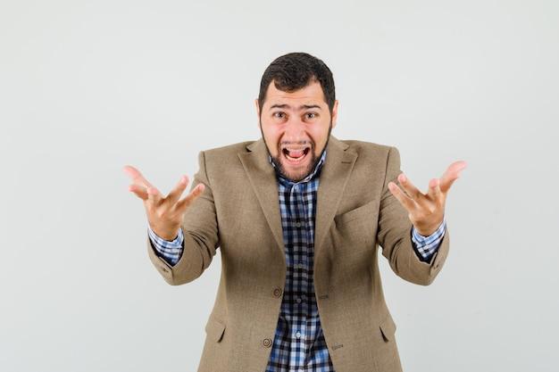 Junger mann, der hände in der fragenden geste im hemd, in der jacke anhebt und wütend, vorderansicht schaut.