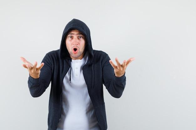 Junger mann, der hände in der fragenden geste im t-shirt, in der jacke und in der verwirrten vorderansicht streckt.