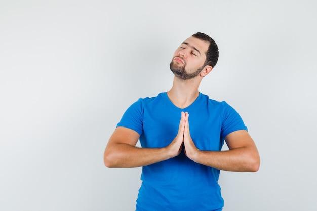 Junger mann, der hände in der gebetsgeste im blauen t-shirt hält und friedlich schaut
