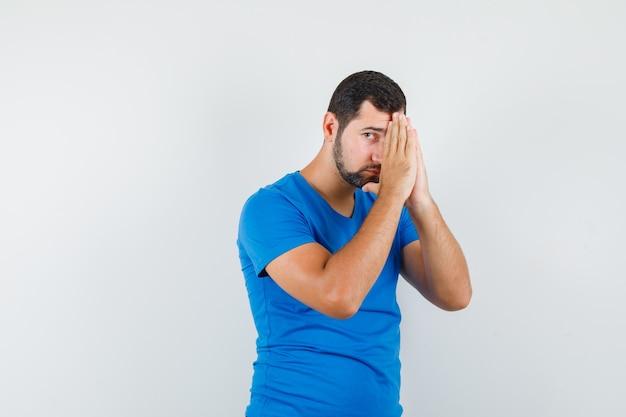 Junger mann, der hände in der gebetsgeste im blauen t-shirt hält und hoffnungsvoll schaut