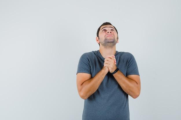 Junger mann, der hände in der gebetsgeste im grauen t-shirt fasst und hoffnungsvoll aussieht