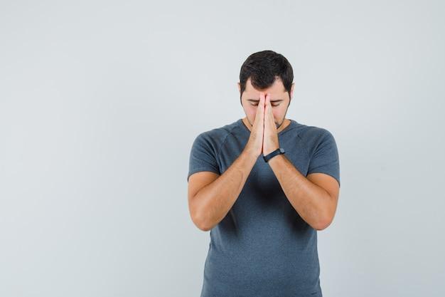 Junger mann, der hände in der gebetsgeste im grauen t-shirt hält und hoffnungsvoll aussieht