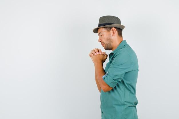 Junger mann, der hände in der gebetsgeste im hemd fasst