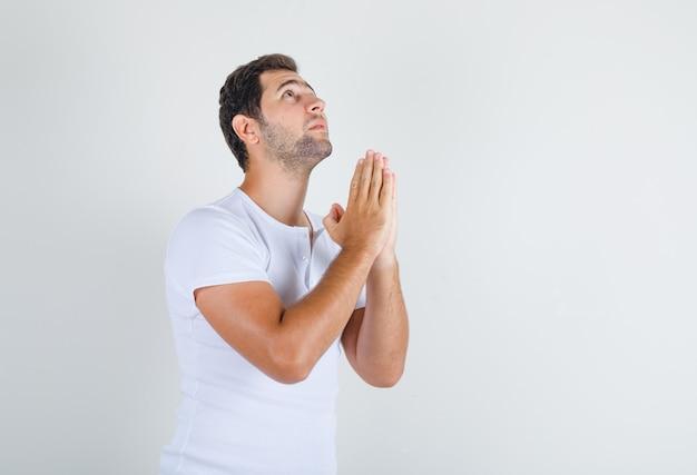 Junger mann, der hände in der gebetsgeste im weißen t-shirt hält und hoffnungsvoll schaut