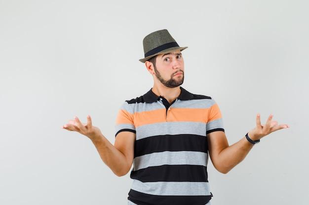 Junger mann, der hände in der verwirrten geste im t-shirt, im hut und im zweifelhaften blick erhebt.