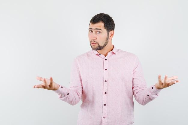 Junger mann, der hände in fragender weise im rosa hemd erhebt und verwirrt schaut