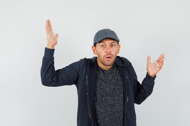 Junger mann, der hände in verwirrter geste in t-shirt, jacke, mütze erhebt