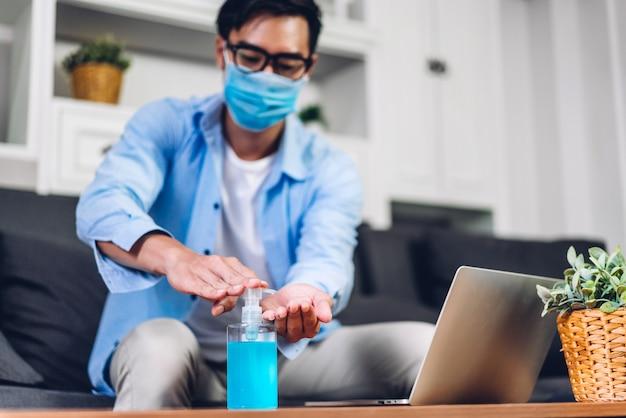 Junger mann, der hände mit alkoholgel in quarantäne für coronavirus trägt, das schutzmaske trägt