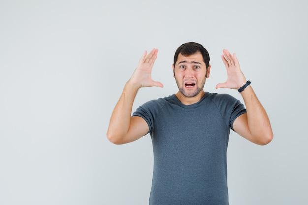 Junger mann, der hände nahe kopf im grauen t-shirt hält und traurig schaut
