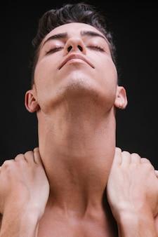 Junger mann, der hals massiert