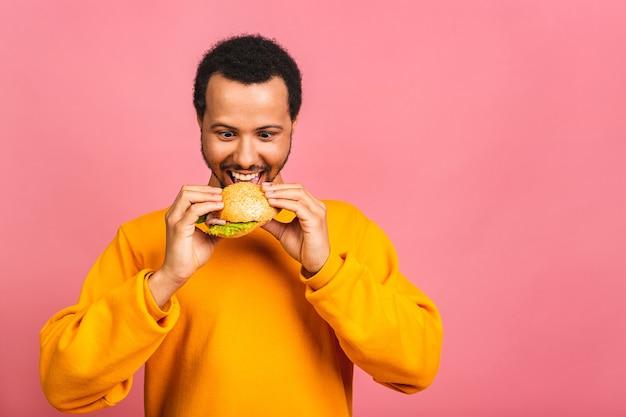Junger mann, der hamburger isst, isoliert über rosa. diätkonzept.