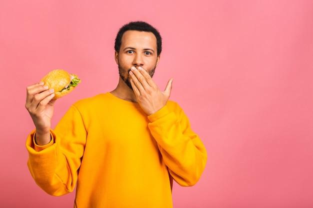 Junger mann, der hamburger isst, isoliert über rosa