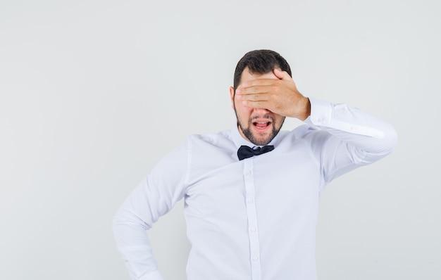 Junger mann, der hand auf augen im weißen hemd hält und aufgeregt, vorderansicht schaut.