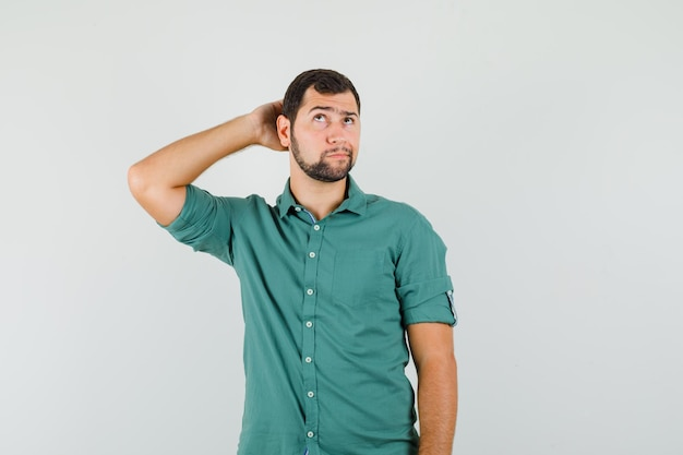 Junger mann, der hand auf dem kopf hält, während er im grünen hemd aufschaut und nachdenklich aussieht. vorderansicht.