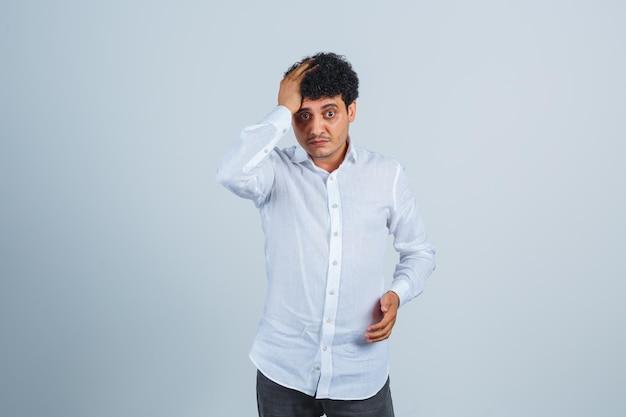 Junger mann, der hand auf dem kopf im weißen hemd hält und wehmütig, vorderansicht schaut.