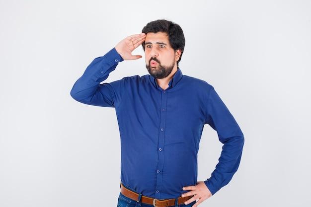 Junger mann, der hand auf der stirn hält, während er im königsblauen hemd wegschaut, vorderansicht.