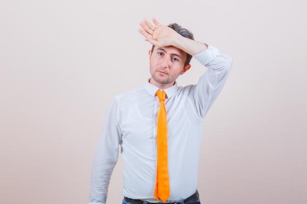 Junger mann, der hand auf der stirn in hemd, krawatte, jeans hält und nachdenklich aussieht