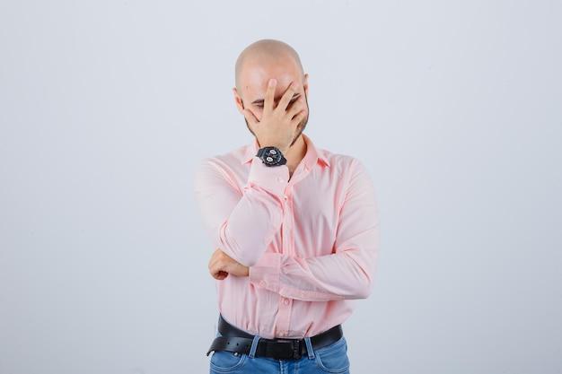 Junger mann, der hand auf gesicht hält, während er in rosa hemd lächelt, vorderansicht der jeans.