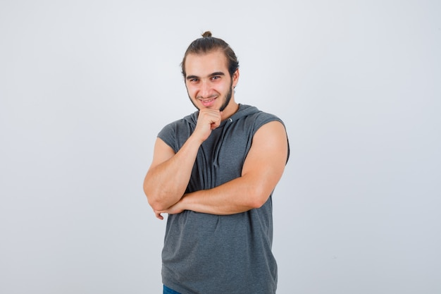 Junger mann, der hand auf kinn im kapuzen-t-shirt hält und erfreut, vorderansicht schaut.