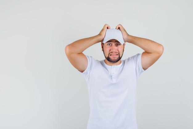 Junger mann, der hand auf kopf im weißen t-shirt, in der kappe hält und beunruhigt schaut. vorderansicht.
