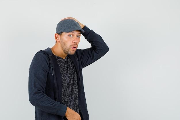 Junger mann, der hand auf kopf in t-shirt, jacke, mütze hält und überrascht schaut. vorderansicht.
