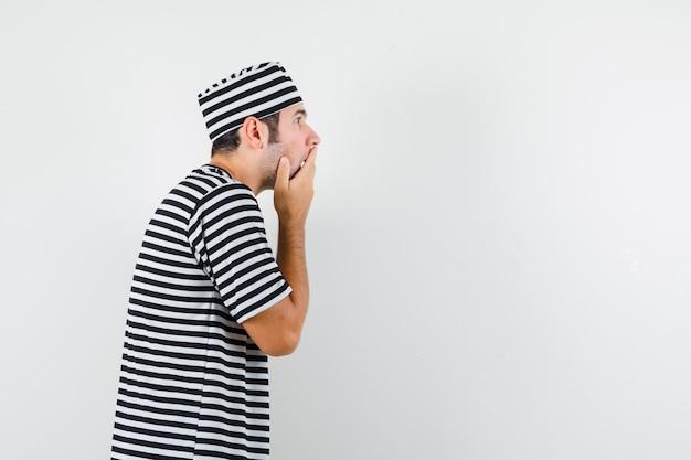 Junger mann, der hand auf mund im t-shirt, hut hält und überrascht schaut. .