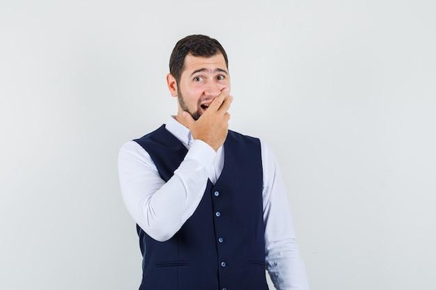 Junger mann, der hand auf mund in hemd, weste hält und überrascht schaut