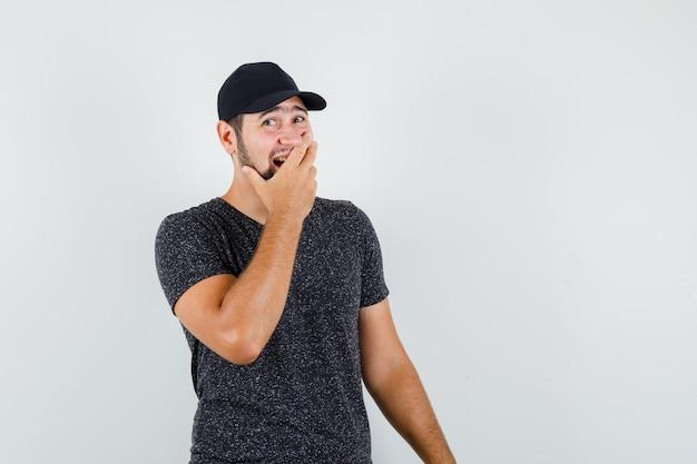 Junger mann, der hand auf mund in t-shirt und mütze hält und fröhlich schaut