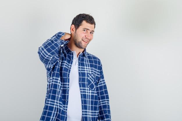 Junger mann, der hand auf seinem hals im hemd hält und fröhlich aussieht.