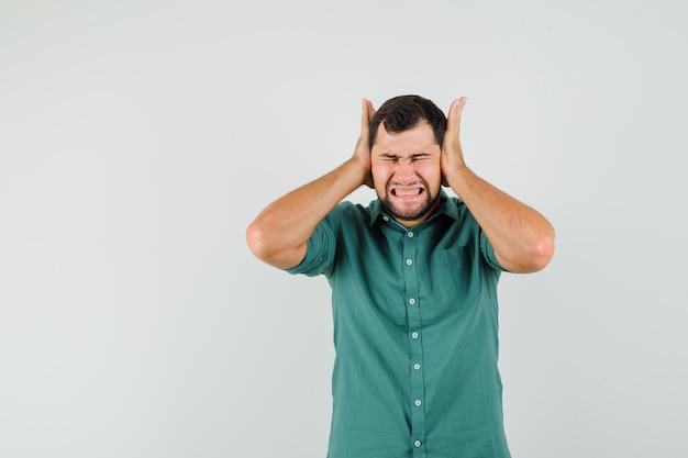 Junger mann, der hand auf seinem kopf im grünen hemd hält und gelangweilt aussieht. vorderansicht.