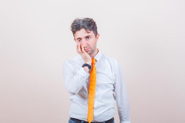 Junger mann, der hand auf wange in weißem hemd, jeans hält und verzweifelt aussieht