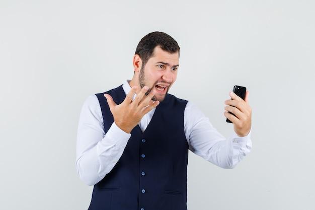 Junger mann, der hand erhöht, während video-chat in hemd und weste verwendet wird und aggressiv aussieht