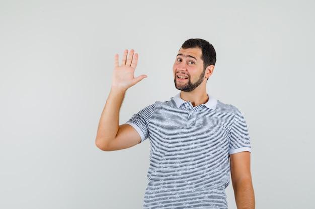 Junger mann, der hand für gruß im t-shirt winkt und fröhlich, vorderansicht schaut.