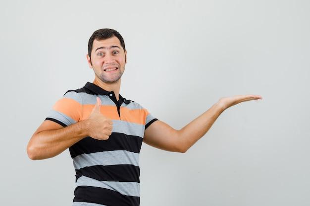Junger mann, der hand hebt, um etwas zu zeigen, während daumen oben im t-shirt zeigt und fröhlich aussieht. platz für text
